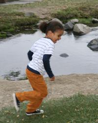 Little boy running by a pond